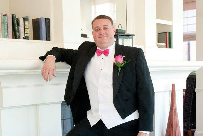 Will Feuer leaning against fire place in a tux. The photo is from his wedding.