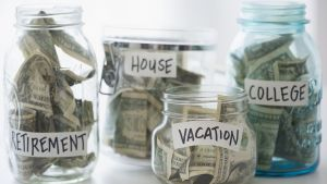 Jars for vacation, house, retirement and college savings with money in them